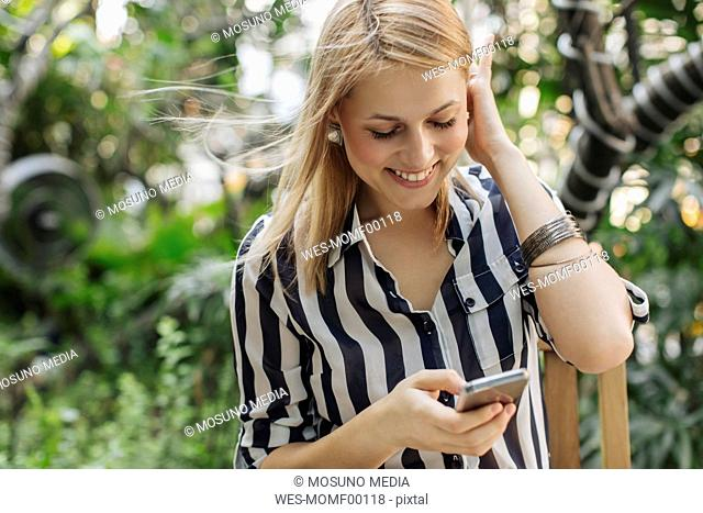 Happy blond woman looking at her smartphone
