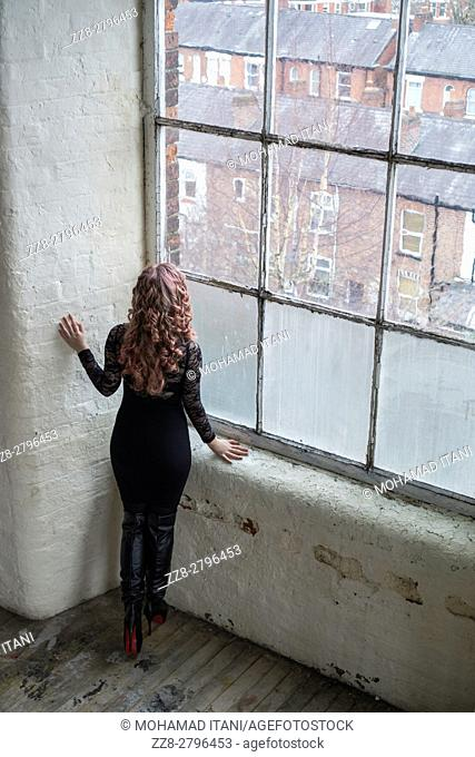 Redhead woman in leather boots looking out of the window