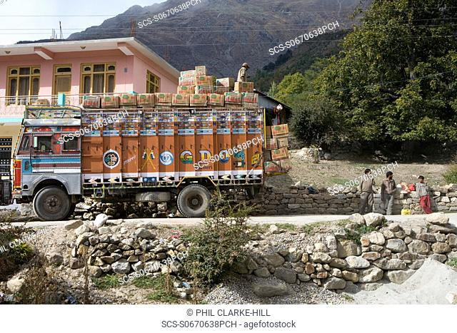 Adult male Indian truckers standing on and around a large truck overloaded with crates of apples with mountains in the background, Kinnaur district