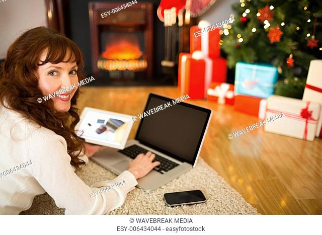 Pretty woman lying on floor using technology at Chritmas