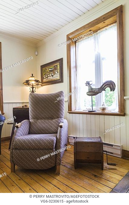 Cloth upholstered armchair in living room inside an old 1892 Canadiana cottage style home