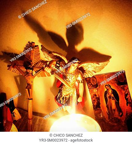 A candle illuminates an altar with an image of Saint Michael Archangel, Jesus Christ crucified and Our Lady of Guadalupe in Colonia Roma, Mexico City, Mexico