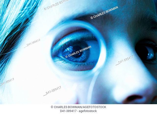 Child's eye seen through magnifying glass