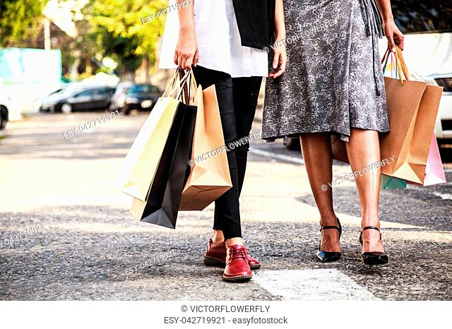 Female Ladies carrying Colorful Shopping Bags in the parking lots Concept