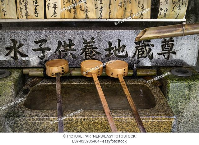 Kyoto, Japan - Row of bamboo ladles at a purificaton basin in front of the shinto temple