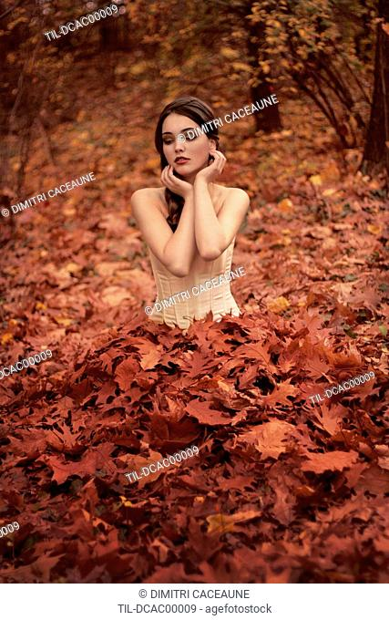 Young woman with long dark hair outdoors wearing a corset sitting in fallen autumn leaves