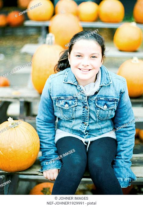 Smiling girl with pumpkins in background, New Jersey, USA