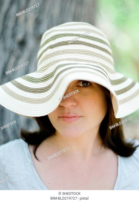 Close up of serious woman wearing sun hat