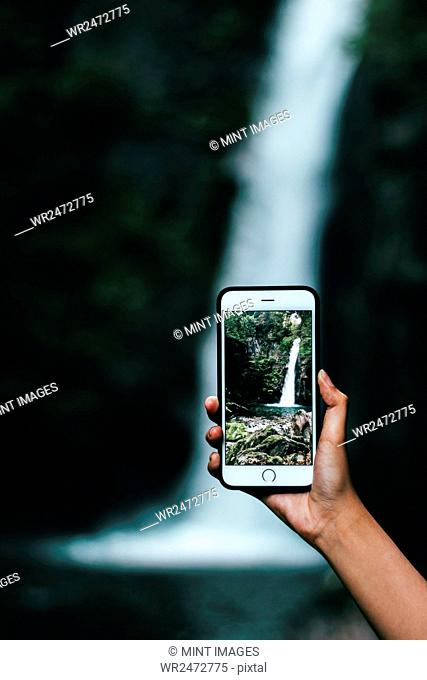 Woman holding a smart phone, taking a photograph of a waterfall