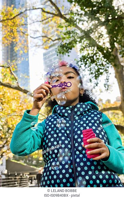 Girl blowing bubbles, New York, USA