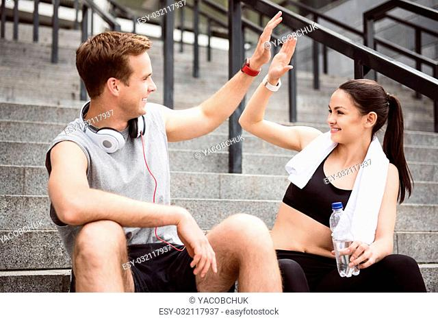 Give me five. Contended young man giving five to lovely young woman while sitting on the stairs after doing sports