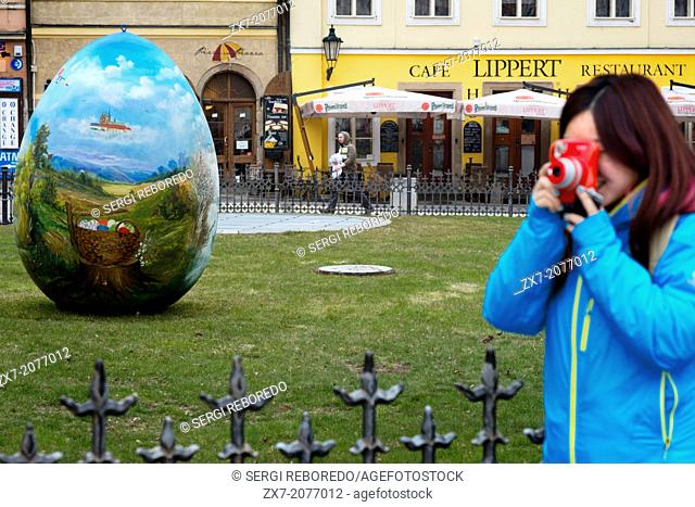 A Japanese take pictures with a Polaroid in the gardens located in front of the Café Lippert front of the Old Town Square