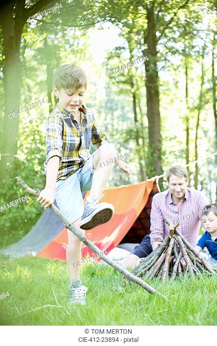Boy breaking stick for campfire with father and brother