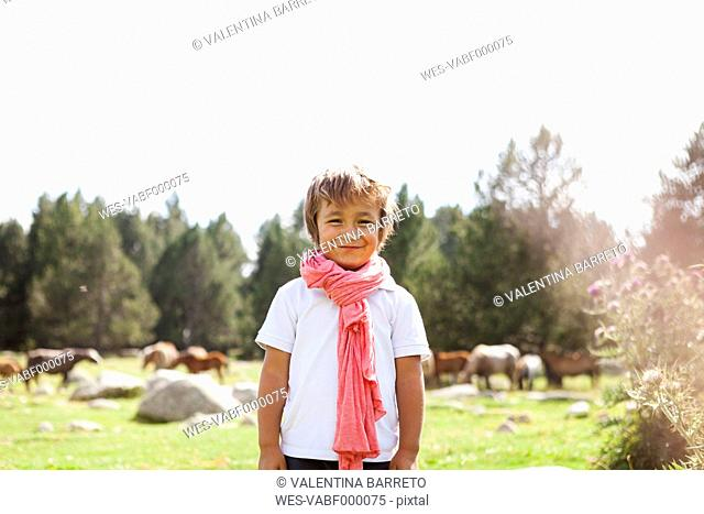 Spain, Cerdanya, portrait of smiling little boy wearing pink scarf