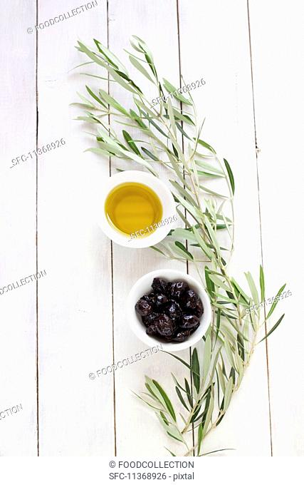 Black olives, olive oil and an olive sprig