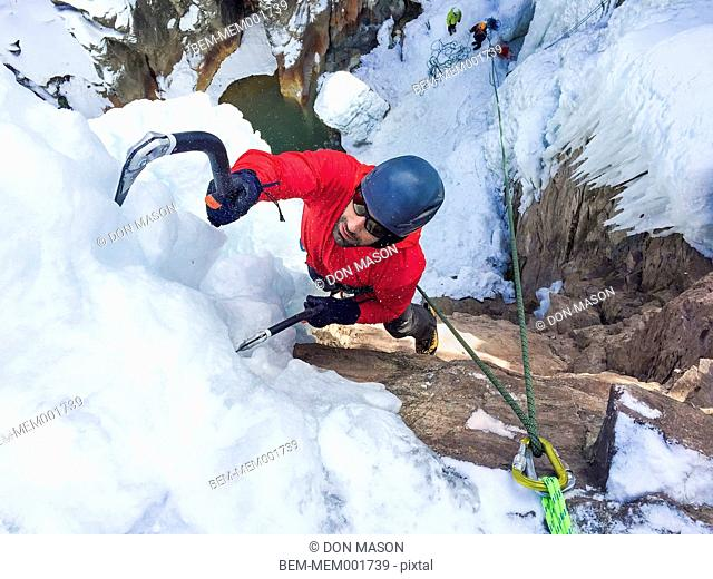 High angle view of Caucasian man ice climbing with hooks