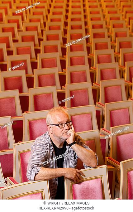 Mature stage designer sitting alone in National Theatre Munich