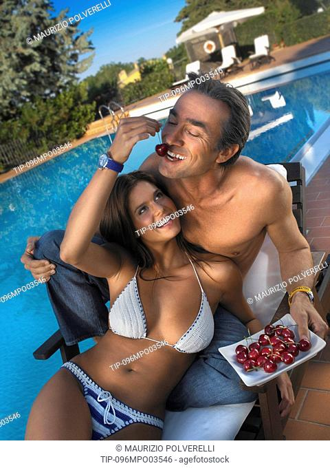 Couple at swimming pool eating cherries