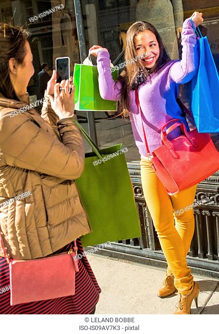 Young female adult twins in city taking smartphone photographs with shopping bags