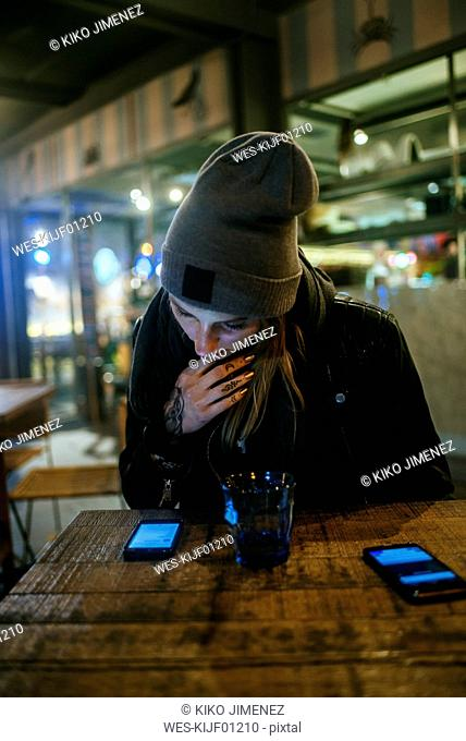 Young woman sitting on the terrace of a bar looking on cell phone