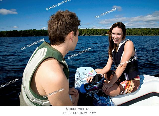 Couple in speedboat with wakeboard