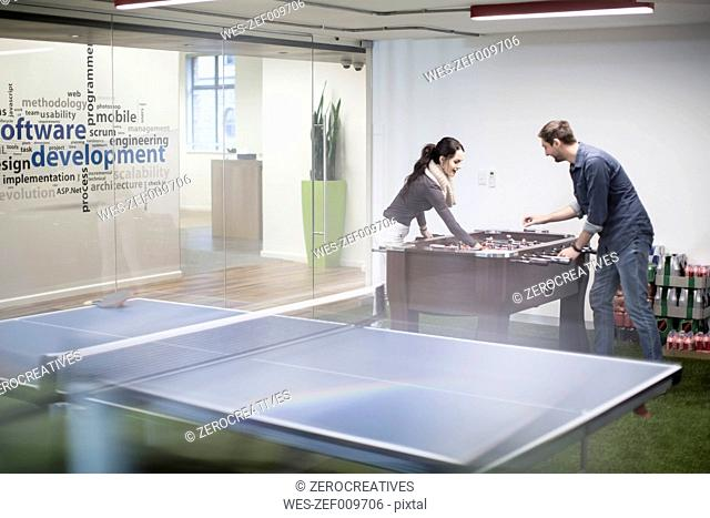 Two colleagues playing foosball in office break room
