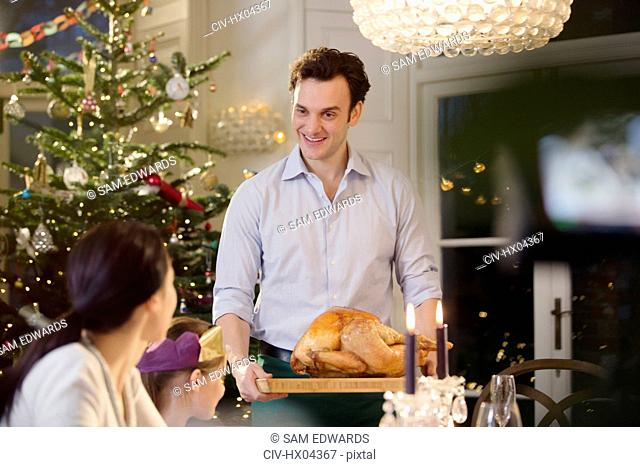 Man serving Christmas turkey to family at candlelight dinner table