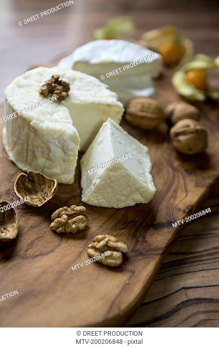 Close-up of cheese and walnuts on chopping board, Germany