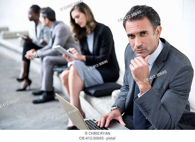 Portrait serious corporate businessman using laptop