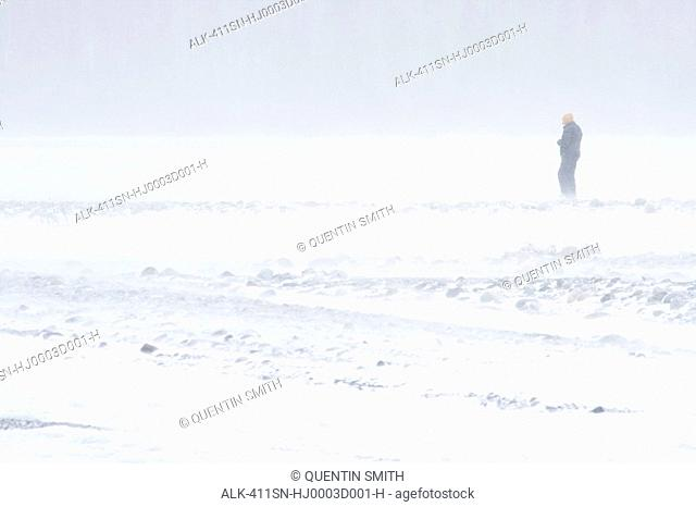 Man walks on the frozen Chitina River close to the Bernard Glacier in Wrangell-St. Elias National Park during Winter in Alaska