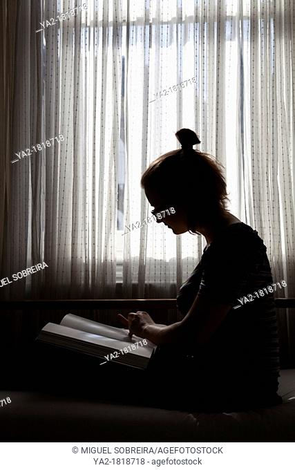 Girl on Settee reading Book