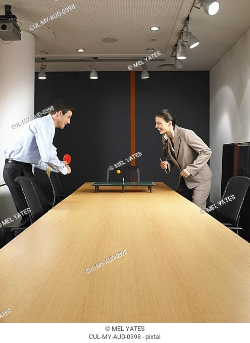 Man and woman playing miniature ping pong at boardroom table