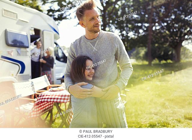 Affectionate father and daughter hugging outside sunny motor home