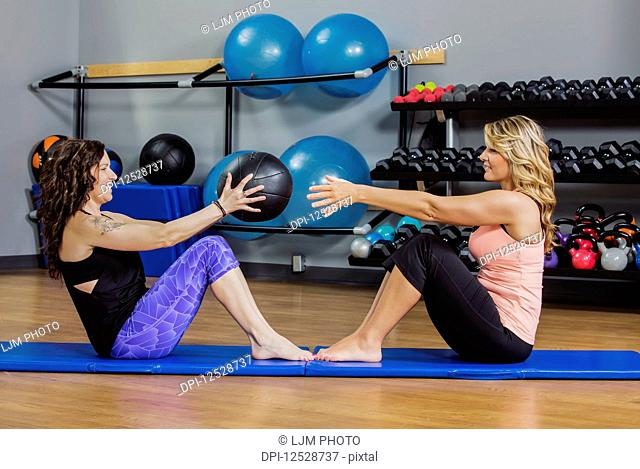 Two attractive middle-aged women working out at the gym together with a medicine ball; Spruce Grove, Alberta, Canada