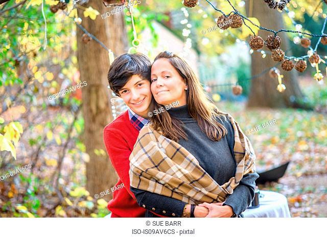 Portrait of teenage son hugging mother in woods