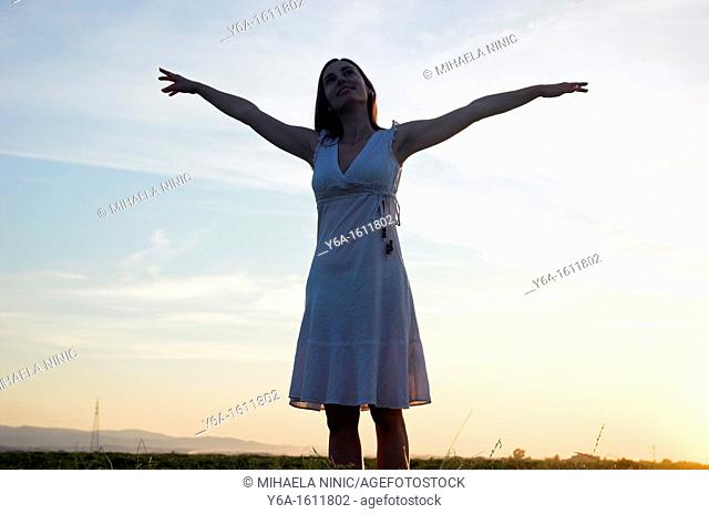 Silhouette of a young woman standing in field at dusk arms raised