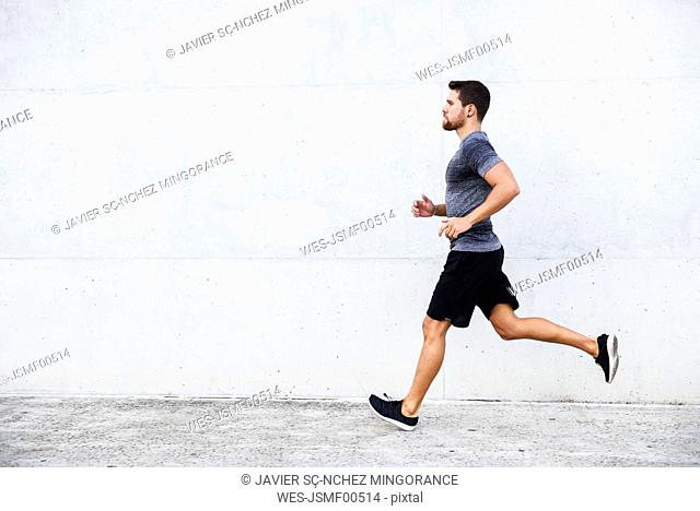 Athlete running in front of white wall