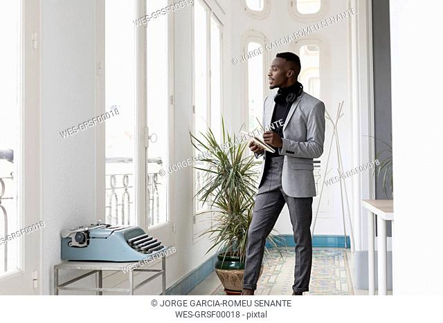 Young businessman standing in office looking out of the window