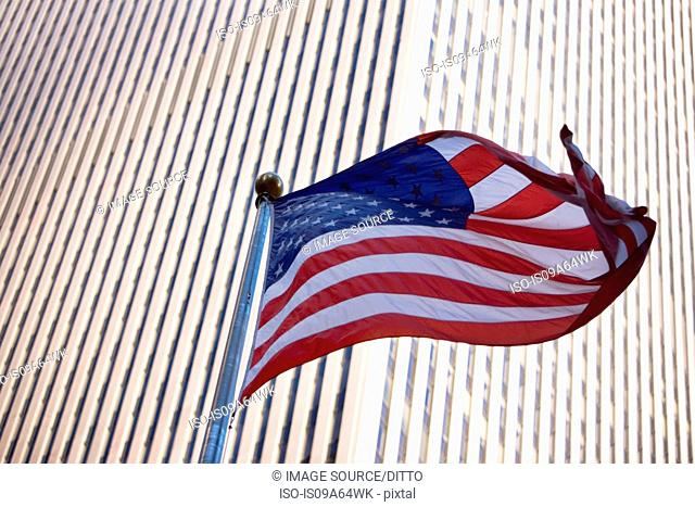 American flag flying by city skyscraper