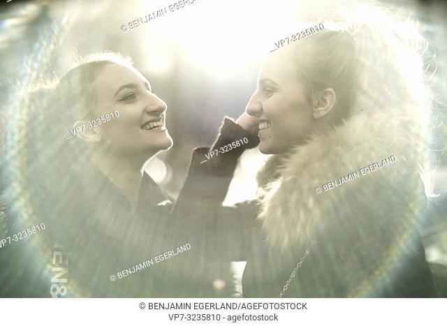 Two teenage sisters in sunlight, Munich, Germany