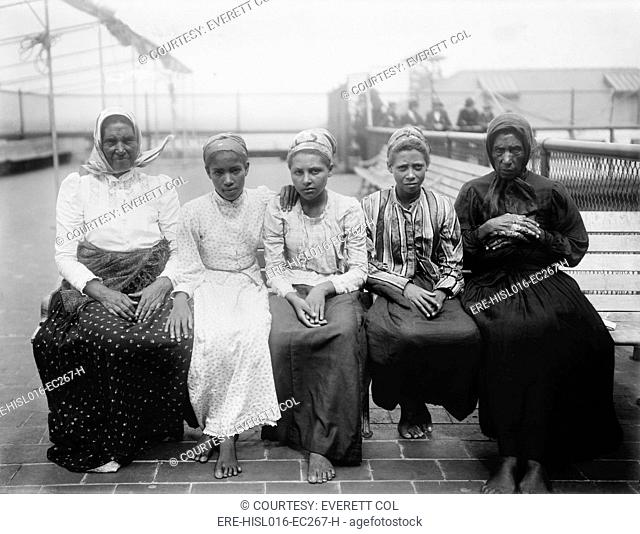 Barefoot women immigrants at Ellis Island are from the Caribbean. Ca. 1910