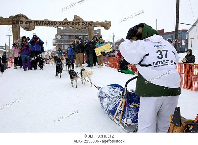 Christine Roalofs runs into the chute and across the finish line to finish in last place and is the winner of the Red Lantern Award on Front Street in Nome