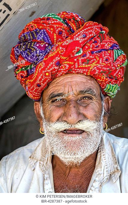 Rajasthani wearing traditional dress and turban at the Pushkar Mela camel fair, Pushkar, Rajasthan, India