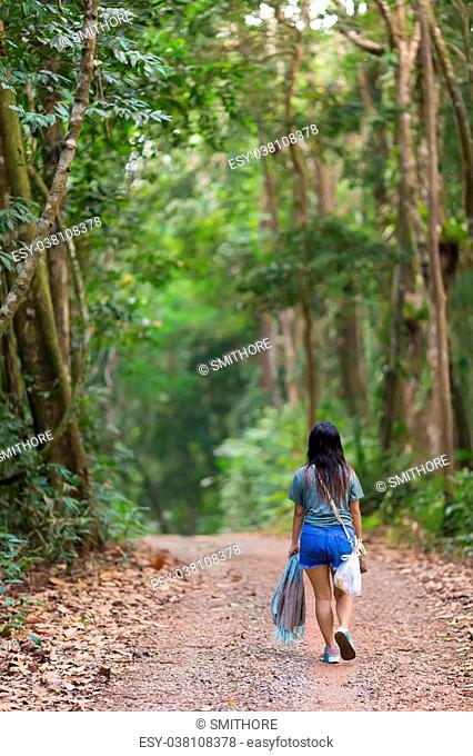 Woman walking in a jungle path in the Ko Kood island in Thailand