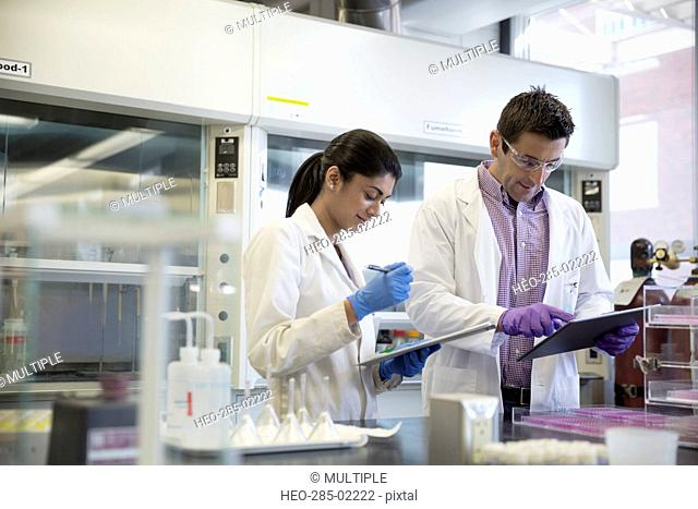 Scientists with digital tablet and clipboard working together in laboratory