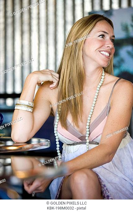 View of a sexy young woman sitting in a cafi