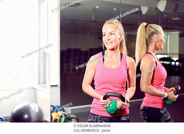 Woman carrying kettlebell in gym