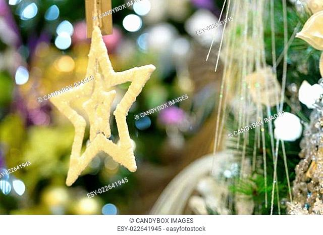 Gold star ornament hanging from Christmas tree