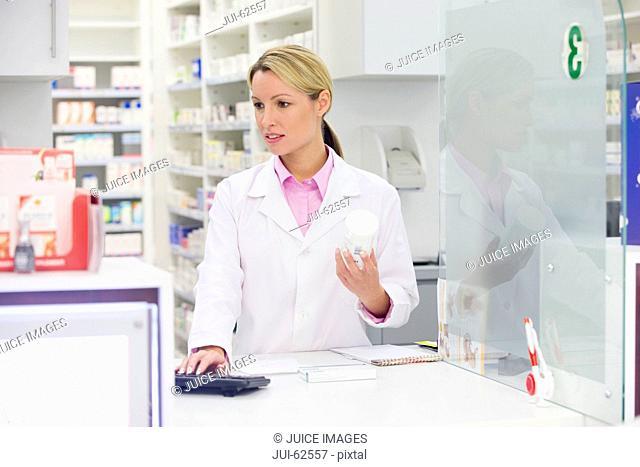 Pharmacist holding prescription medication at pharmacy counter