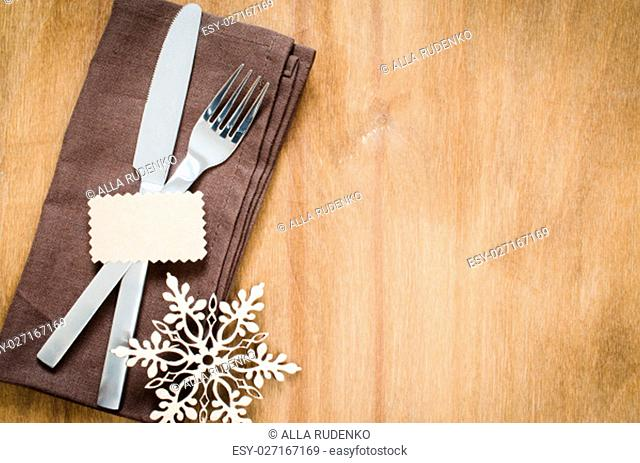 Winter Table Setting. Silverware with Empty Tag and Linen Napkin on Rustic Wooden Background. Top View. Copy Space. Selective Focus